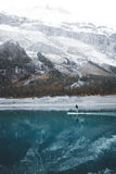 Paddle-boarder on lake by glacier Stock Photo