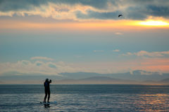 Paddle boarder at sunset Stock Photo