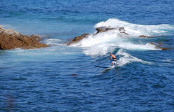 Standup paddle boarder surfing off Heisler Park, Laguna Beach, California. Stock Photo