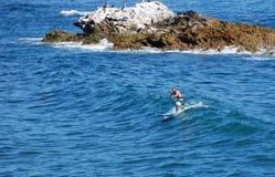 Standup paddle boarder surfing off Heisler Park, Laguna Beach, California. Stock Photos
