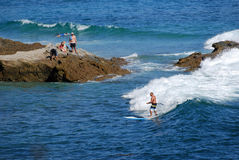 Standup paddle boarder surfing off Heisler Park, Laguna Beach, California. Royalty Free Stock Photography