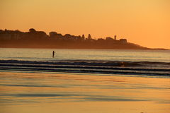 Paddle boarder on waves, with lighthouse in background Stock Photography