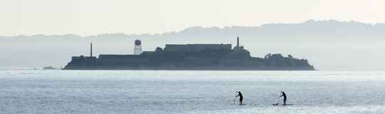 Paddle boarders and Alcatraz. Two paddle boarders silhouetted in front of Alcatraz on a hot San Francisco Bay morning stock photography