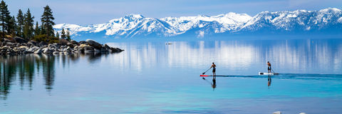 Paddle boarding. Two men stand up paddle boarding Lake Tahoe Royalty Free Stock Photo