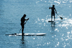 Paddle boards in the sun. Paddleboards with sun reflections in the water stock images