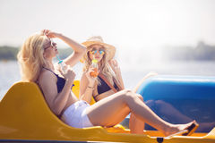 On the paddle boat. A photo of two beautiful friends relaxing on holiday. They're swimming paddle boat and drinking juice Royalty Free Stock Photography