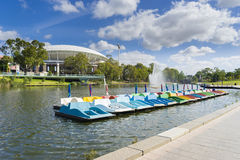 Paddle boats in Adelaide city in Australia. View of row of paddle boats with the stadium in the riverbank of Adelaide city in Australia during daytime royalty free stock image
