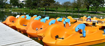Paddle boats docked in a pond Stock Photo