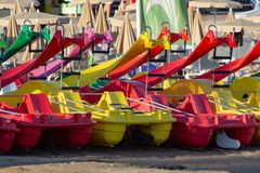 Paddle boats or pedalo for rent on sandy beach, sea vacation. Colorful paddle boats or pedalo for rent on sandy beach, sea vacation stock images