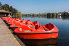 Paddle Boats, Pedalos at Roath Park Lake, Cardiff. A row of red paddle boats, pedalos for recreation parked at Roath Park Lake, Cardiff, Wales, UK stock photo