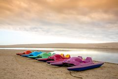 Paddle Boats at River. Colorful paddle boats on the sand next to the lagoon water Royalty Free Stock Photo