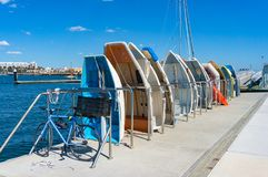 Paddle boats in a row on a pier. Paddle boats in a row with bicycle on the foreground on a pier on sunny day stock images