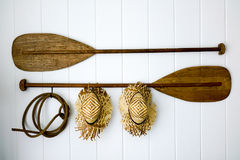 Paddle prop set. Paddle with rope and hat hanging on the white wall royalty free stock image
