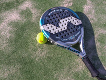 Paddle racket and ball. Paddle racket with yellow ball on an artificial floor Royalty Free Stock Image