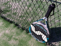Paddle racket and net. Paddle racket supported on a net on a sport court Royalty Free Stock Photography