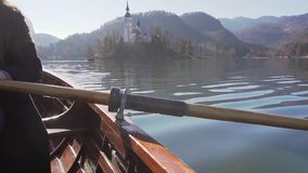 Closeup slow motion of paddle rowing in a boat on lake Bled with island Bled and church behind it and a reflection in. Paddle rowing in a boat on lake Bled on a stock video footage