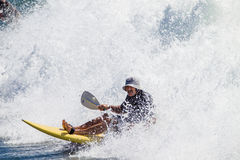 Paddle-Ski Rider White Water. Paddle ski rider straightens out on wave and engulfed by white water from crashing wave Stock Photo
