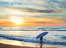 Paddle surfing, Portugal. Man carrying surfboard on the beach at sunset. Sagres, Algarve region, Portugal Stock Photo