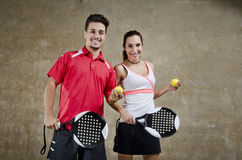 Paddle tennis couple posing in concrete court. Smiling paddle tennis couple posing in concrete court royalty free stock photos