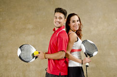Paddle tennis couple posing on concrete wall court Royalty Free Stock Images