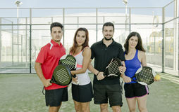 Paddle tennis couples posing for macht. Two couple posing for paddle tennis match in court royalty free stock photos