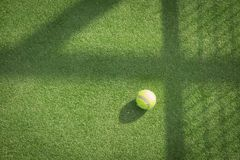 Paddle tennis court and ball. Green grass paddle tennis court and net with a yellow ball on the surface royalty free stock photo