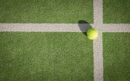 Paddle tennis court and ball. Green grass paddle tennis court and net with a yellow ball on the surface royalty free stock photos