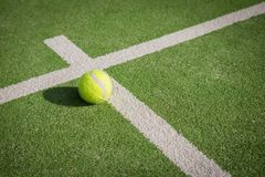 Paddle tennis court and ball. Green grass paddle tennis court and net with a yellow ball on the surface royalty free stock photography