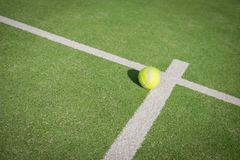 Paddle tennis court and ball. Green grass paddle tennis court and net with a yellow ball on the surface stock photography