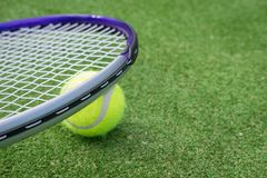 Paddle tennis court and ball. Green grass paddle tennis court and net with a yellow ball on the surface with a tennins racket stock images