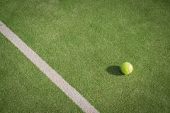 Paddle tennis court and ball. Green grass paddle tennis court and net with a yellow ball on the surface stock photo