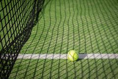 Paddle tennis court and net with a ball on the net shadow Royalty Free Stock Photo