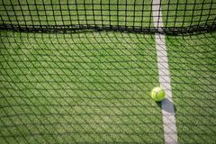 Paddle tennis court and net with a ball on the net shadow Stock Photo