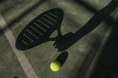 Paddle tennis player shadow in ball in court. In sunny day outdoors image stock photography