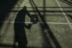 Paddle tennis player shadow in ball in court. In sunny day outdoors image royalty free stock photography