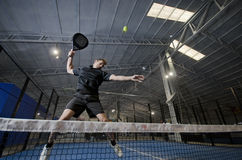 Paddle tennis smash. Paddle tennis player  jumping and smashing ball Royalty Free Stock Photo