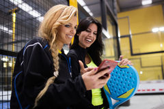 Paddle tennis team using mobile phone after the match. Royalty Free Stock Photos
