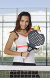 Paddle tennis woman player posing with racket and ball. In outdoors court Stock Images