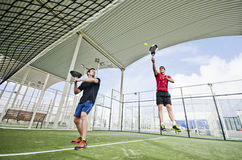 Paddle tnnis players ready for smash. Young paddle tennis player with racket and ball in court stock image