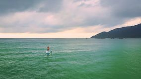 paddleboard的后侧方视图孤立女孩冲浪打开海洋 股票视频