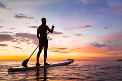 Paddleboard στην παραλία στο ηλιοβασίλεμα, ΓΟΥΛΙΑ, δραστηριότητα ελεύθερου χρόνου στοκ εικόνες με δικαίωμα ελεύθερης χρήσης