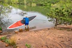 Paddleboard МАЛЕНЬКОГО ГЛОТКА старшего paddler запуская Стоковые Фото