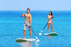 Paddleboard beach people on stand up paddle board. Surfboard surfing in ocean sea on Big Island, Hawaii Beautiful young multi-ethnic couple, mixed race Asian Royalty Free Stock Photos