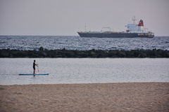 Paddleboard man. Paddleboard beach man on stand up paddle board surfboard surfing near beach Royalty Free Stock Images