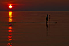 Paddleboarder/κουπί που επιβιβάζεται στο ηλιοβασίλεμα Στοκ φωτογραφία με δικαίωμα ελεύθερης χρήσης