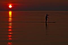 Paddleboarder/embarque de la paleta en la puesta del sol foto de archivo libre de regalías