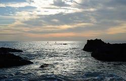 Paddleboarders al tramonto vicino alla spiaggia in Laguna Beach, California della baia di legni immagine stock libera da diritti