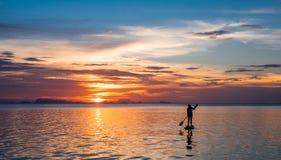paddleboarding在日落的女孩 免版税库存图片
