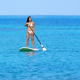 Paddleboarding beach woman on stand up paddleboard. Surfboard surfing in ocean sea on Big Island, Hawaii. Beautiful young multiracial Asian Caucasian woman in Stock Photos