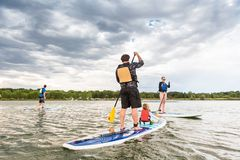 Paddleboarding. Denver, Colorado, USA-July 23, 2016. Family paddleboarding on small pond Stock Photography